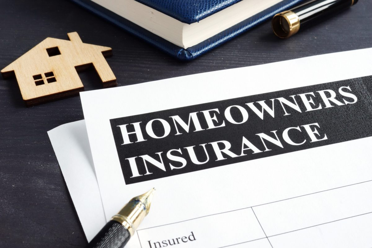 Homeowners insurance policy and model of home.